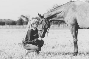 Mare and owner on stubble field saying goodbye